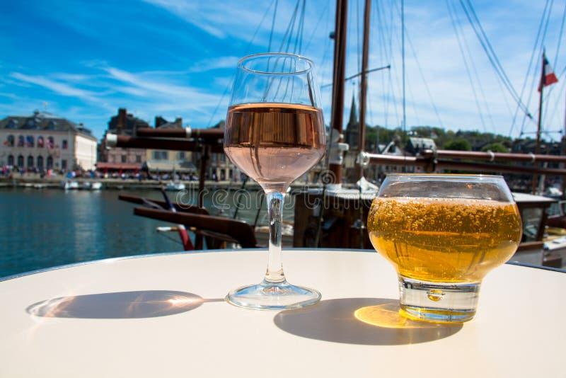 玻璃用鲜美苹果汁和玫瑰色藤在老法国fisherm 库存照片