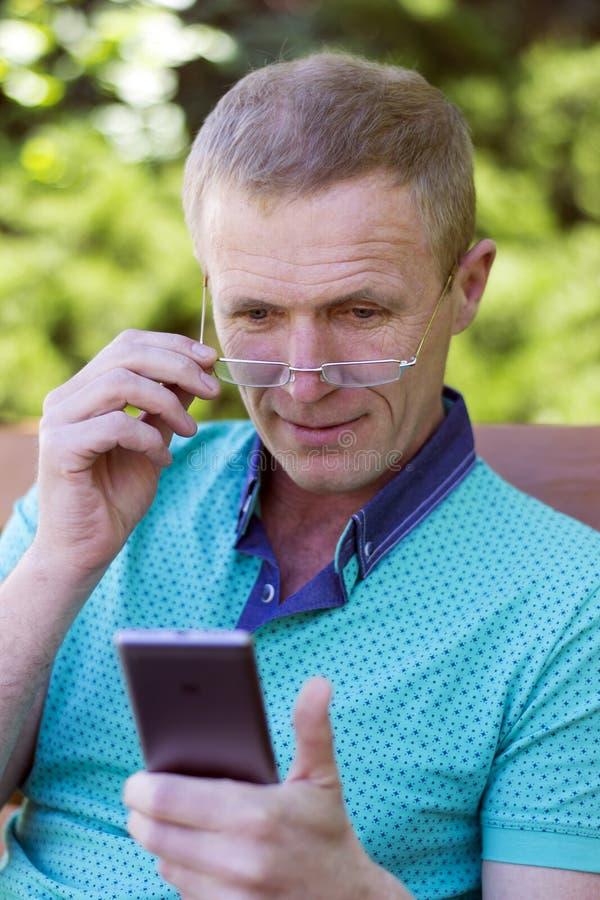 玻璃的人与电话 免版税库存照片