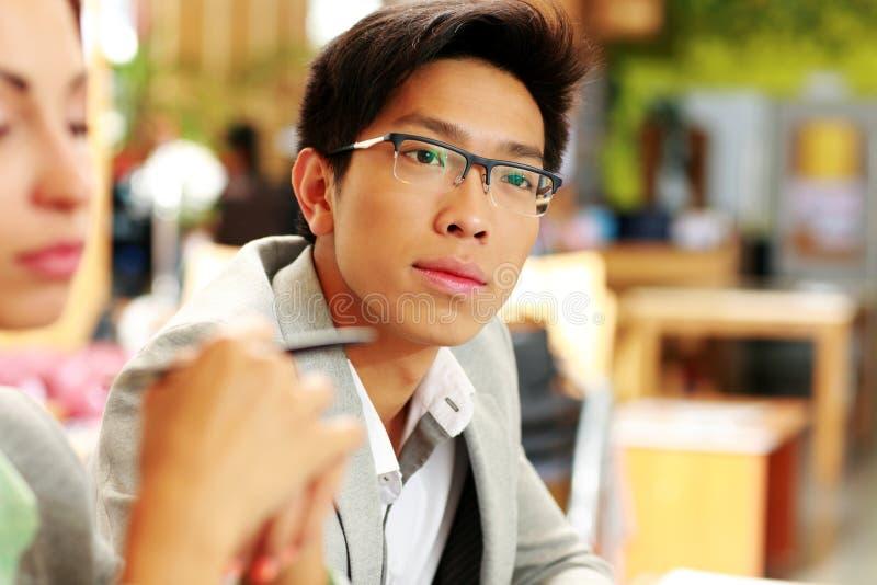 玻璃的体贴的亚裔人在办公室 免版税库存照片