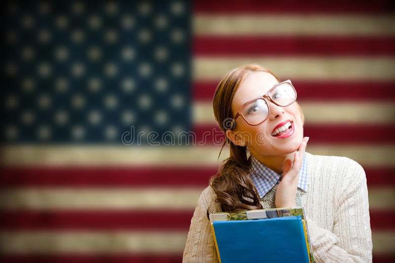 玻璃的俏丽的学生女孩微笑在美国旗子的 免版税图库摄影
