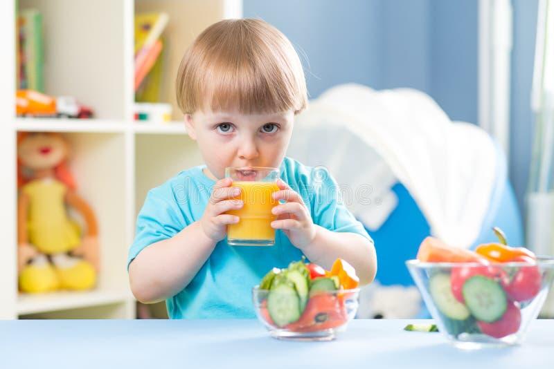 从玻璃的儿童男孩饮用的汁液户内 免版税库存图片