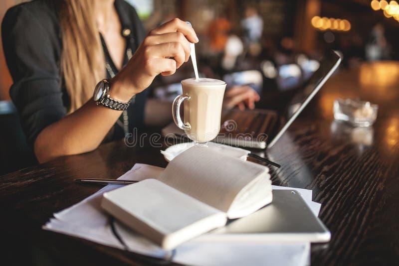 玻璃的女商人室内用采取笔记的咖啡和膝上型计算机在餐馆 图库摄影