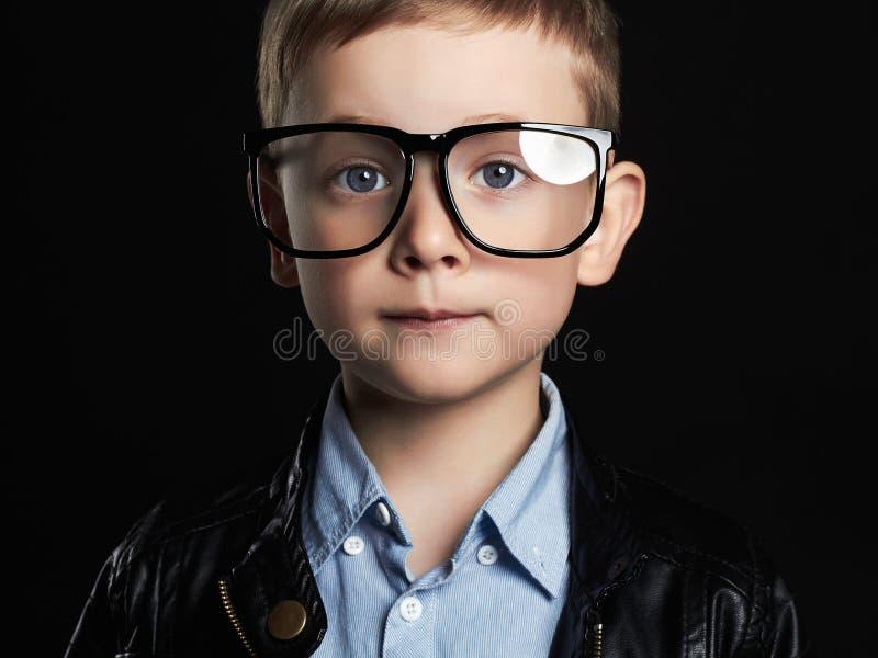 玻璃的小男孩 时髦皮革外套的滑稽的孩子 免版税库存照片