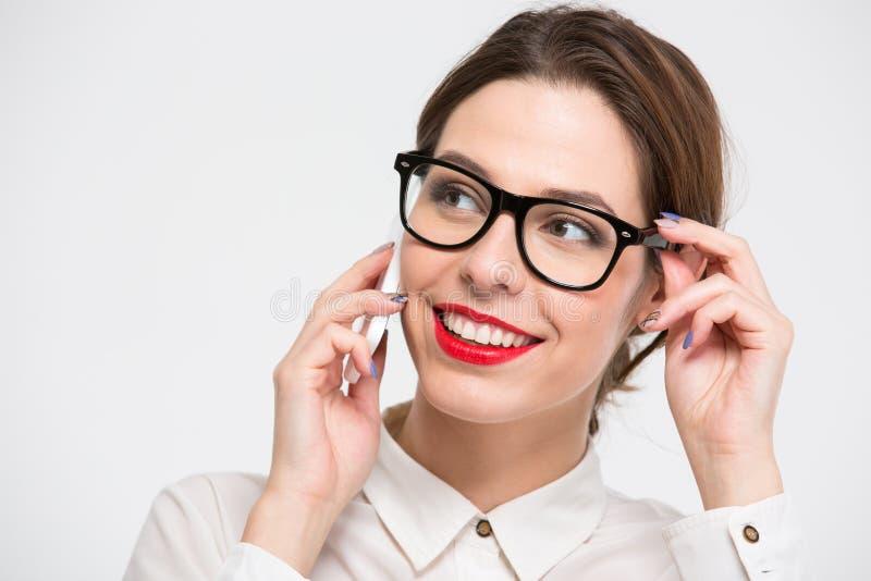 玻璃的快乐的俏丽的女商人谈话在手机 免版税库存图片