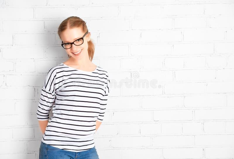玻璃的愉快的女学生在一个空白的白色砖墙 免版税库存照片
