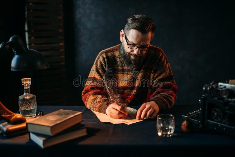 玻璃的有胡子的作家写与羽毛 库存照片