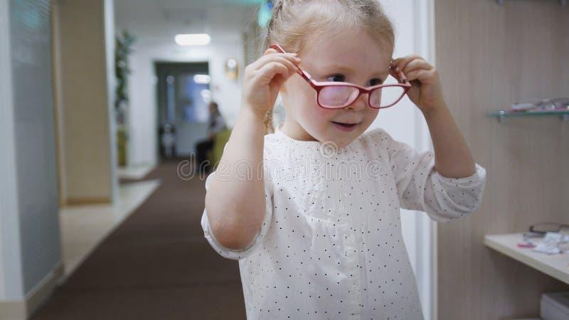 玻璃的白肤金发的小女孩在眼科学的诊所大厅里医疗- 免版税库存图片