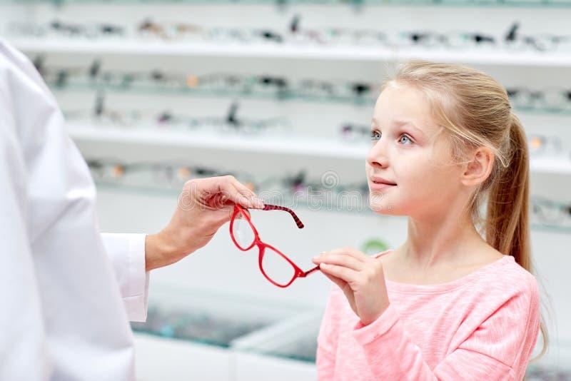 给玻璃的眼镜师女孩在光学商店 免版税库存图片