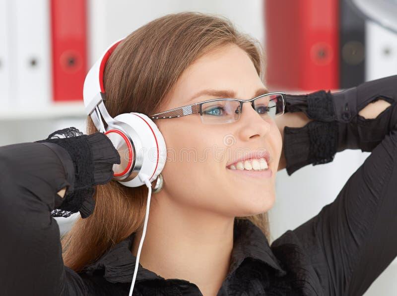 玻璃的美丽的女孩用她的在她的听到在耳机的音乐的头后的手 库存图片