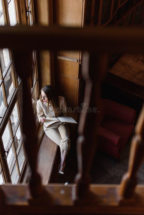 玻璃的美丽的时髦的企业夫人在窗台读一本书 免版税库存照片