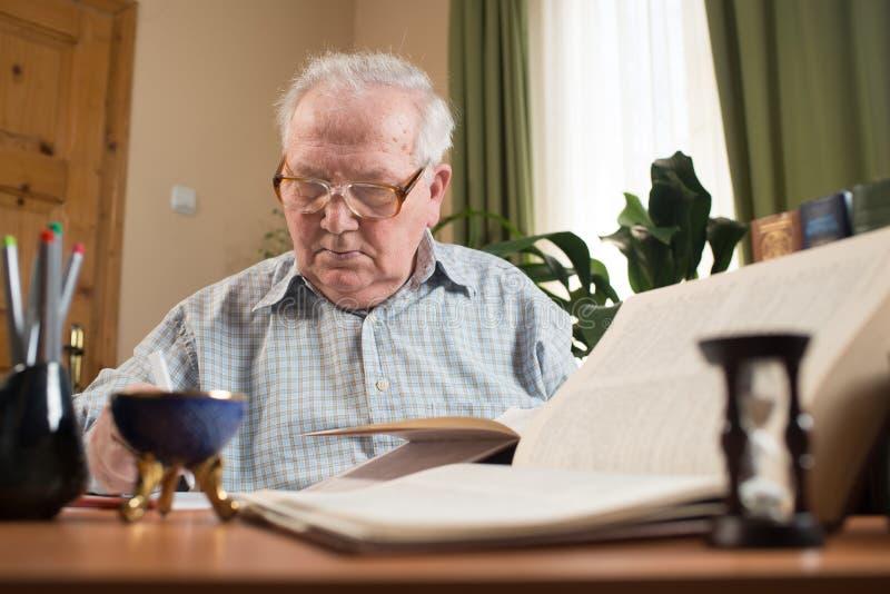 玻璃的老人写从书的在屋子里 图库摄影