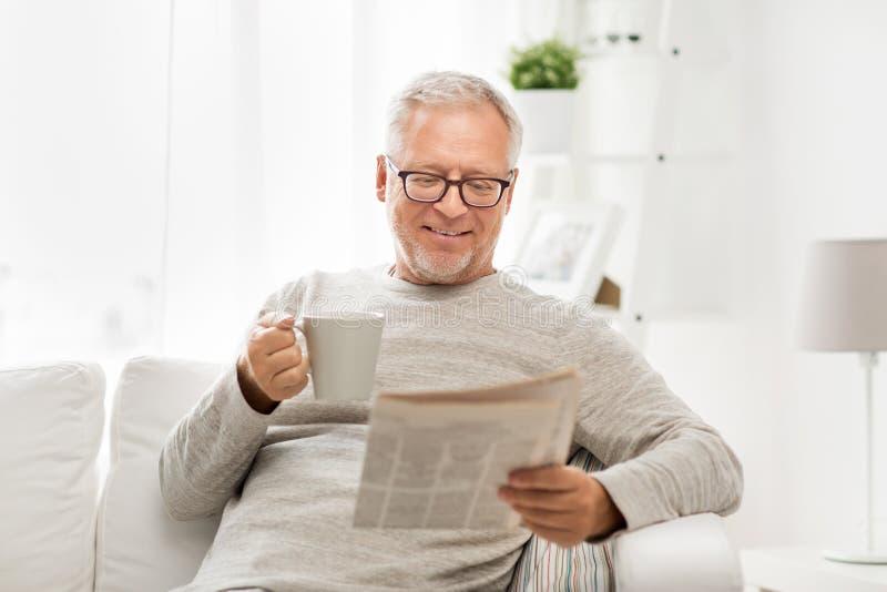 玻璃的老人在家读报纸的 免版税库存照片