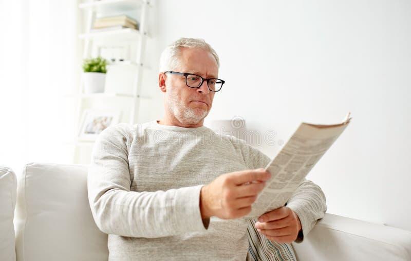 玻璃的老人在家读报纸的 免版税图库摄影