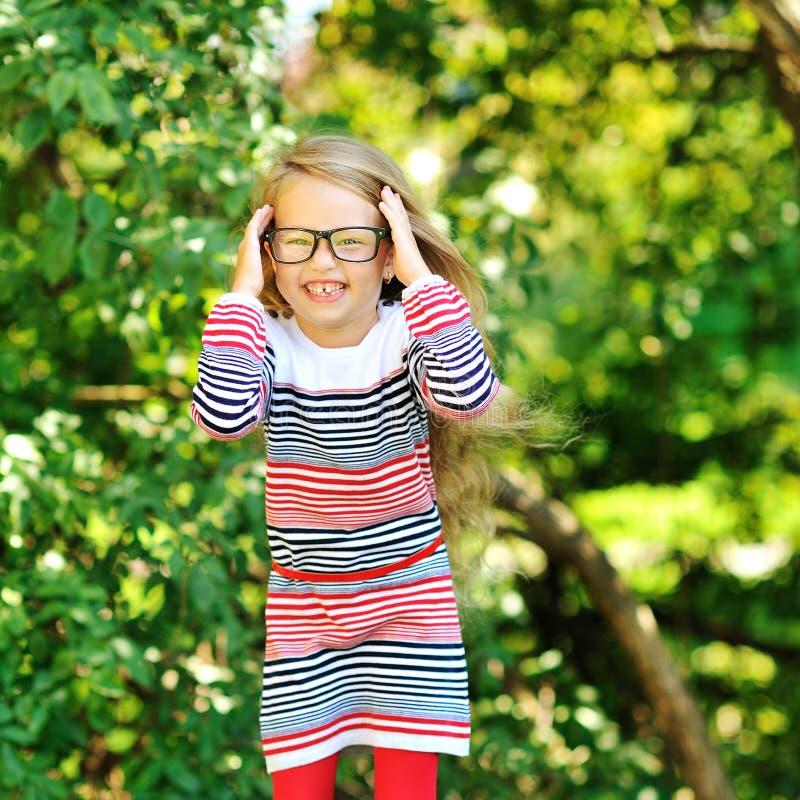 玻璃的逗人喜爱的愉快的小女孩 免版税库存照片