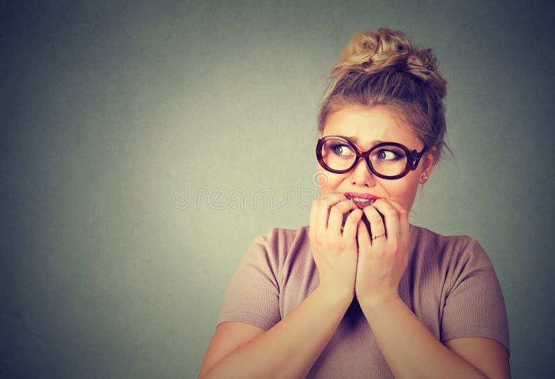 玻璃的紧张的被注重的年轻讨厌的妇女咬住指甲盖的急切地看 免版税库存图片