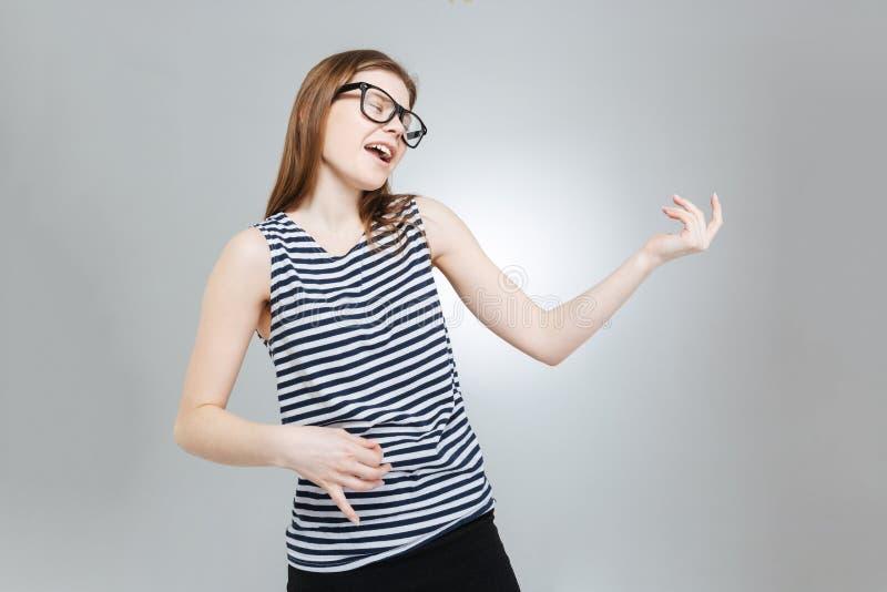 玻璃的仿效逗人喜爱的可爱的十几岁的女孩弹吉他 免版税图库摄影