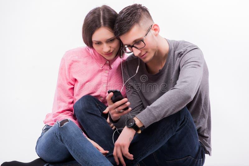 玻璃的年轻行家坐下男人和的妇女和听音乐 免版税库存照片