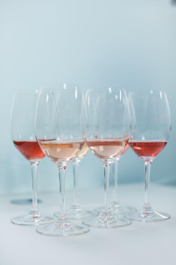 玻璃行用白色和玫瑰酒红色为品尝做准备 免版税库存图片