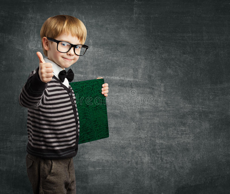 玻璃赞许的小学生,孩子男孩举行书 免版税库存照片