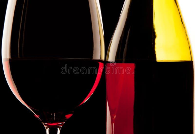 玻璃酒和酒瓶的由后面照的细节反对sol 库存图片