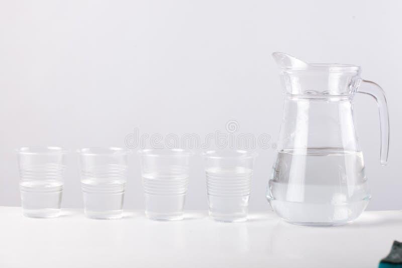 玻璃水罐用在白色背景隔绝的水 库存图片