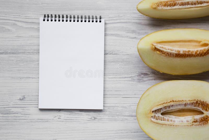 瓜切片和空白的笔记薄在白色木背景,顶上的看法 从上,平的位置 文本的空间 免版税库存图片