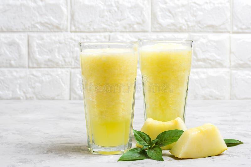 瓜柠檬水、圆滑的人与冰和蓬蒿在一块玻璃在灰色桌上 夏天刷新和戒毒所饮料土气样式 图库摄影