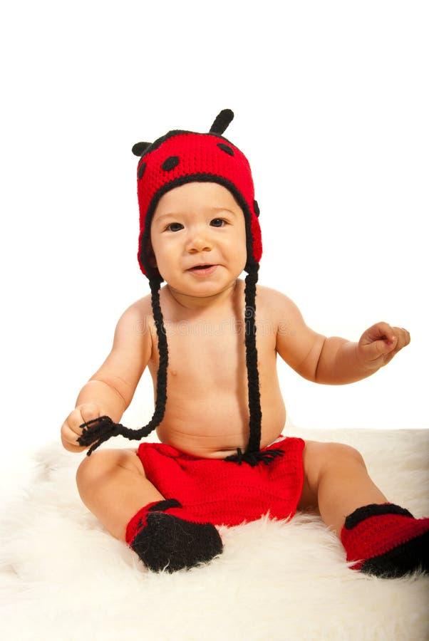 瓢虫帽子和起动的男婴 免版税库存图片