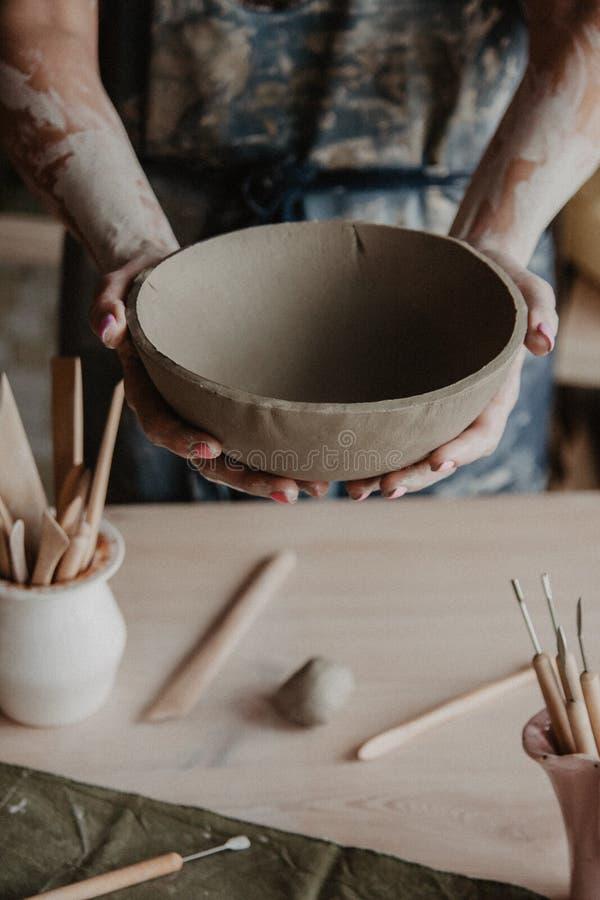 瓦器,黏土,陶瓷艺术概念-在年轻大师的手上的特写镜头与大板材的从火坭 免版税库存照片