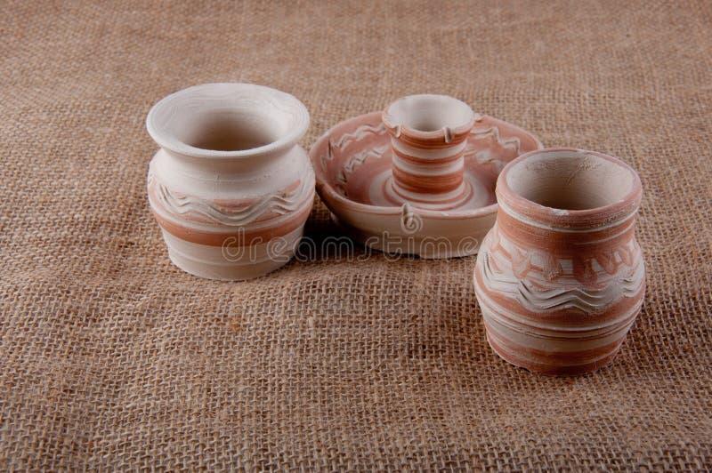 瓦器 水罐和烛台由黏土制成在麻袋布背景 免版税库存照片