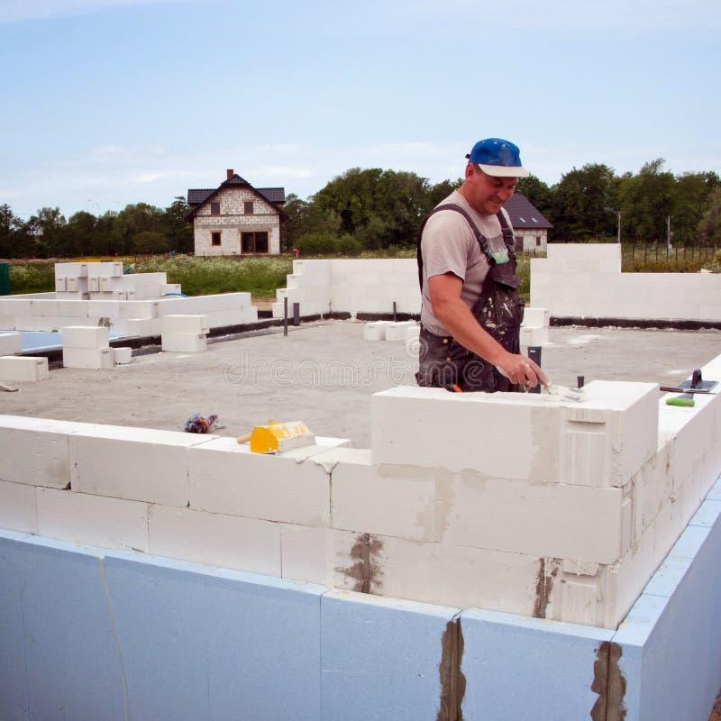 瓦工从被供气的具体块的大厦墙壁 库存照片