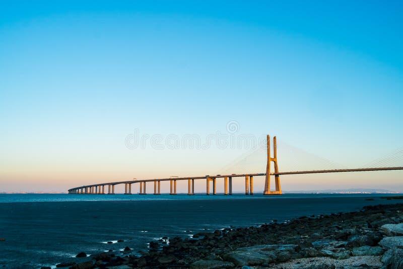 瓦斯科・达伽马在日落期间的` s桥梁与清楚的天空 免版税库存照片