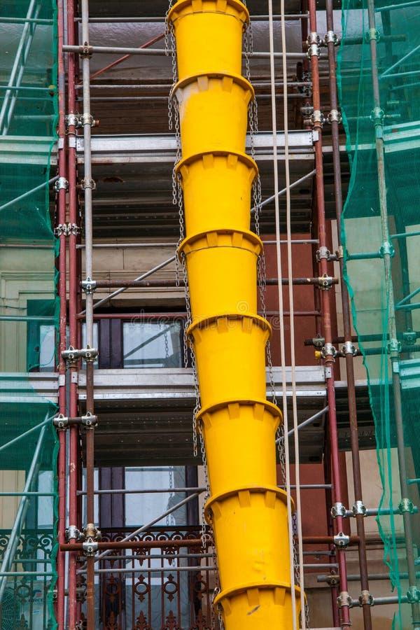 瓦砾在大厦建设中或整修的外在façade的排水管 免版税库存照片