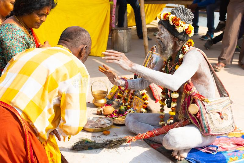 瓦腊纳西,印度,2019年3月10日-身份不明的印度Sadhu圣洁者,坐ghat在恒河附近在瓦腊纳西 图库摄影