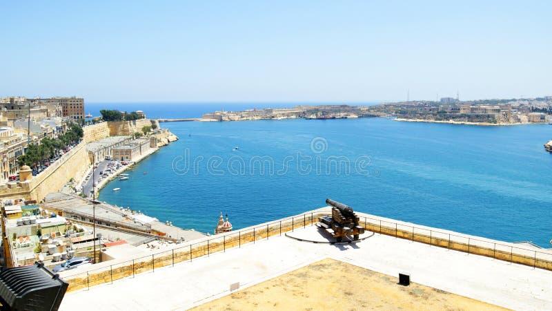 瓦莱塔,马耳他盛大港口  与本营,从上部Barrakka庭院的看法的中世纪堡垒 从老堡垒的古色古香的大炮 免版税库存图片