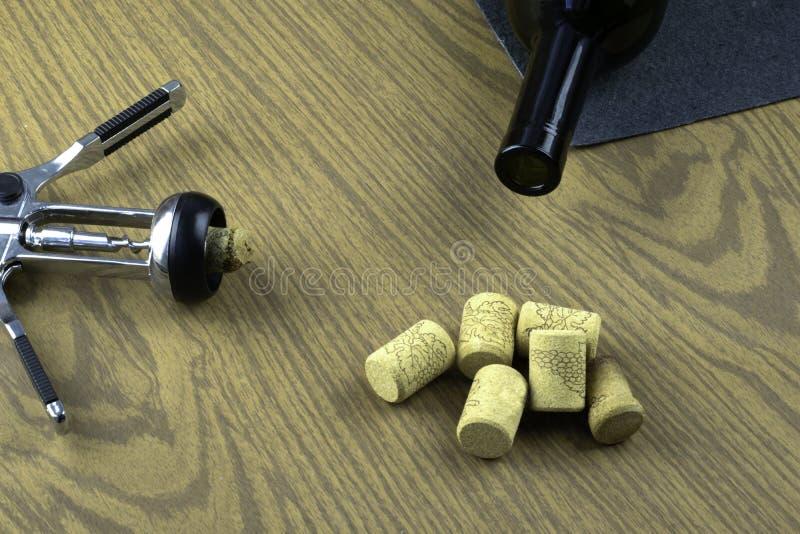 瓶、拔塞螺旋和黄柏在桌上 库存照片