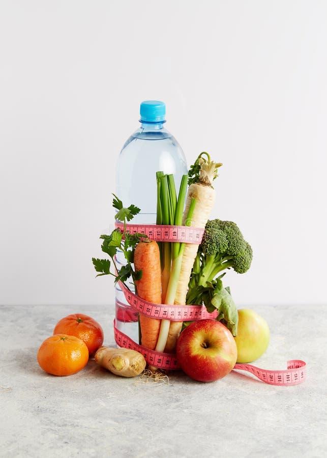 瓶与一卷桃红色测量的磁带、菜和果子的水 库存照片