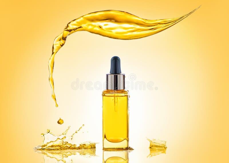 瓶与大飞溅上面和许多的黄色化妆油嬉水 免版税图库摄影