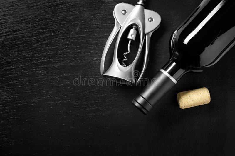 瓶与拔塞螺旋的红酒在黑暗的背景 库存图片