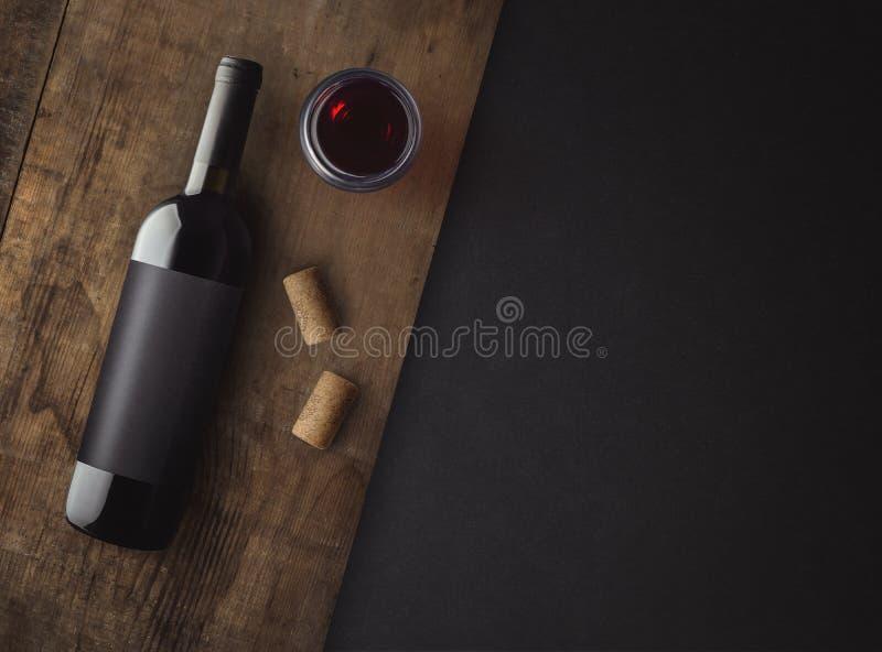 瓶与标签的红葡萄酒在老委员会 杯酒和黄柏 酒瓶大模型 免版税库存图片