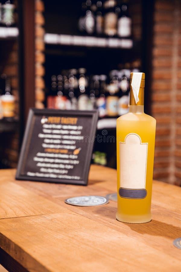 瓶与标签的黄色limoncello和在酒铺的白色盖帽在巴塞罗那 免版税库存图片