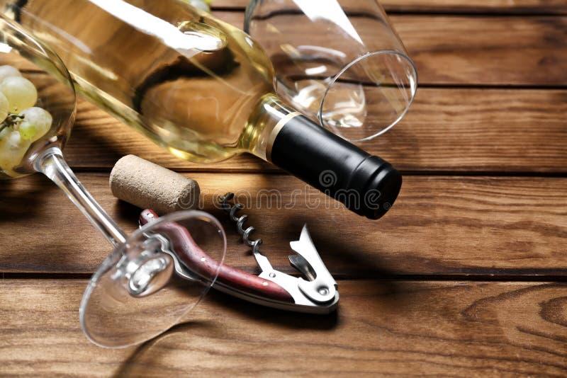 瓶与玻璃和拔塞螺旋的白酒在木桌上 免版税库存图片