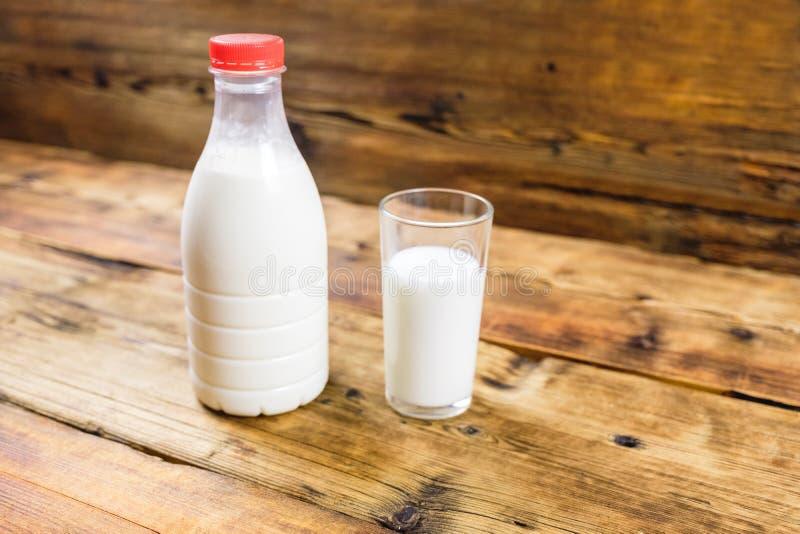 瓶与红色盒盖和杯的新鲜的农厂牛奶在木背景的牛奶在照片的中心 免版税库存图片