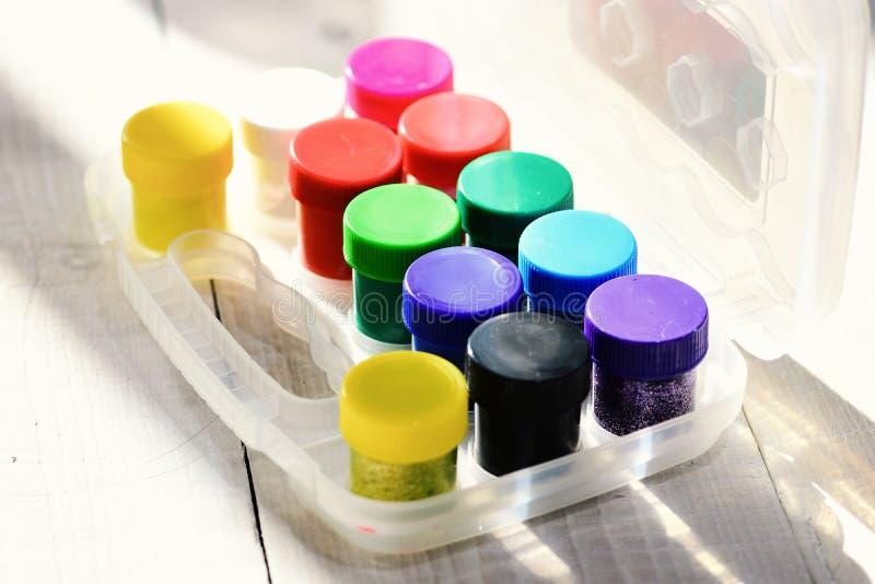 瓶与闪烁的树胶水彩画颜料在透明箱子 免版税库存照片