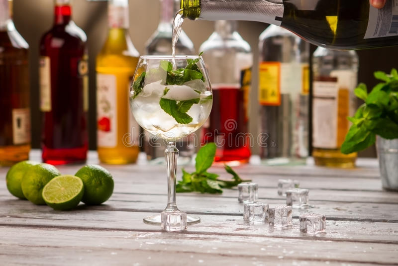瓶倾吐在葡萄酒杯的液体 免版税库存图片