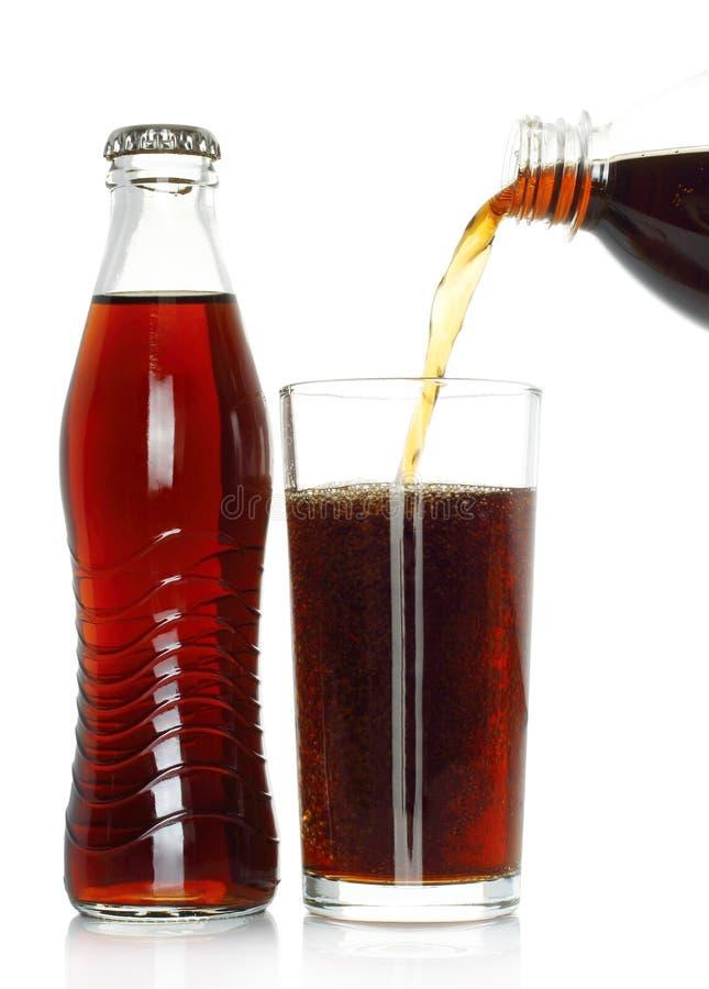 瓶可乐用涌入玻璃的可乐 免版税库存照片
