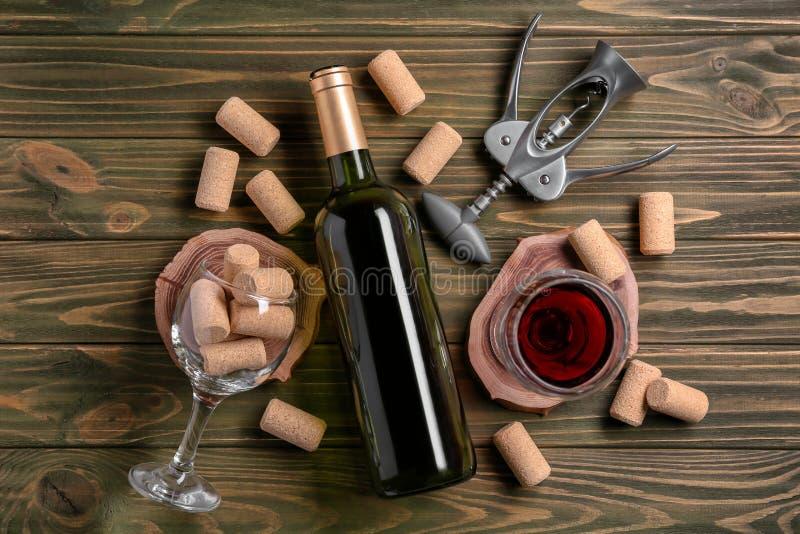 瓶和杯与拔塞螺旋的红酒在木背景 免版税库存图片