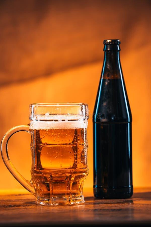 瓶和杯与熏制的乳酪辫子的新鲜的明亮的啤酒在木桌上 免版税库存图片