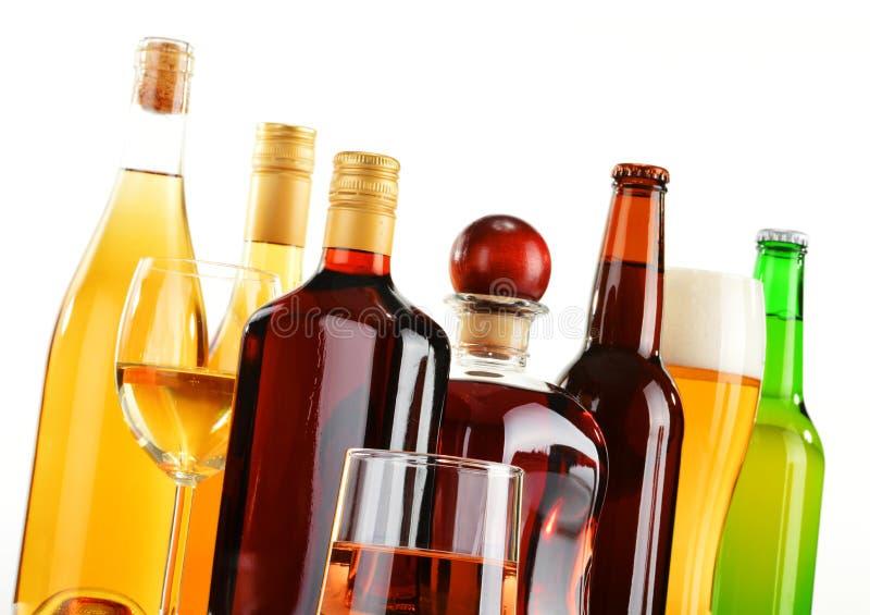 瓶和杯在白色的被分类的酒精饮料 免版税库存图片
