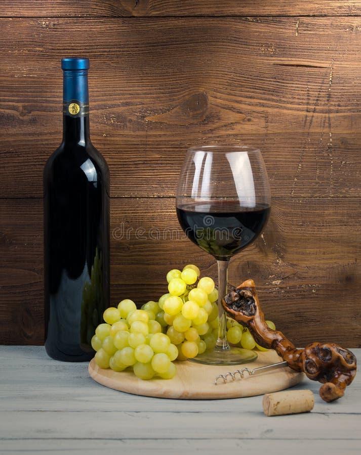 瓶和杯红葡萄酒、葡萄和拔塞螺旋由藤制成 库存照片